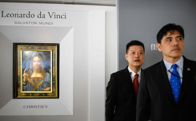 中情局前華裔特工李春興(右)任職香港佳士得公司期間,負責保安工作。圖為2017年佳士得拍賣達文西名畫「救世主」前,曾在香港預展,當時李春興在場戒護。(Getty Images)