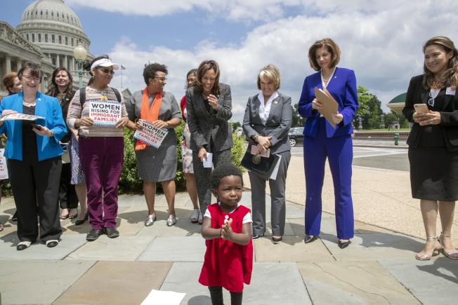 來自莫三鼻克18個月大的坦碧(前)站在國會議員賀錦麗和「天下母親」成員一起為移民家庭請命。(美聯社)