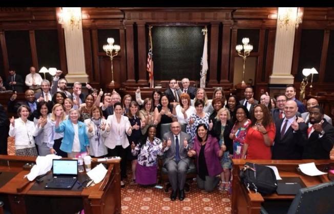 伊州眾議會30日通過「平權修正案」後,支持議員聚集比起大拇指稱讚。(馬靜儀臉書截圖)