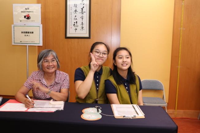 駐休士頓台北經文處處長陳家彥的兩位千金陳冠妤(右)、陳柏妤(中)也加入慈濟義工行列。