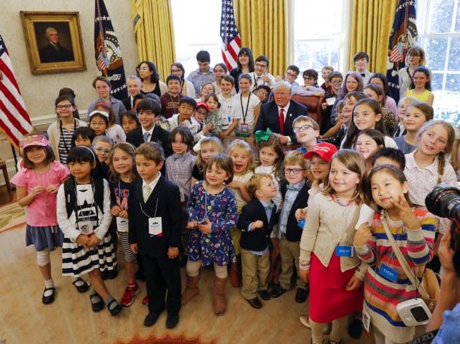 白宮4月底舉行「帶兒女上班」活動,小朋友開心地在橢圓辦公室與川普總統(中)合照。(歐新社)