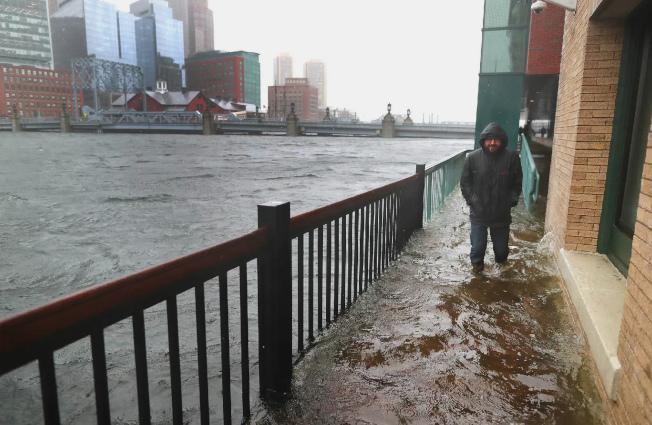 波士頓海港區近年進行多起大型興建工程,已遭質疑在易發生洪患區過度開發。圖為一名男子行經海港區一處沒入水中的行人道。(美聯社)