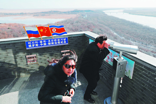 遊客在中國吉林省琿春市的中、朝、俄三國邊界處,透過望遠鏡觀看北韓景色。(路透)