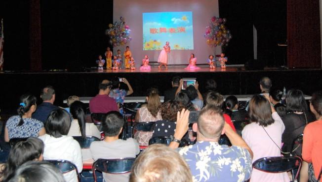 華夏中文學校學生在台上表演,家長在台下猛拍照。