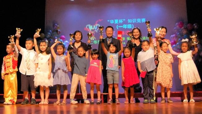 華夏中文學校理事長馬沙(後左一)、中國駐休士頓總領館僑務組領事易川(後左二)、總校長黃玲(後右一)等,頒獎給「華夏杯」青少年中華文化傳承比賽獲獎的同學。
