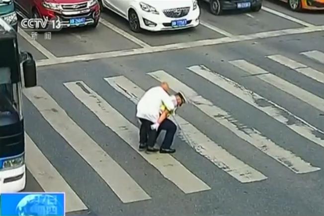 中國四川省綿陽一位老人於4日早上過馬路,儘管步履蹣跚速度緩慢,但在場汽車駕駛均耐心等候,直到交警趕來將他背到馬路中央的雙黃線,汽車駕駛才陸續發動引擎。CCTV
