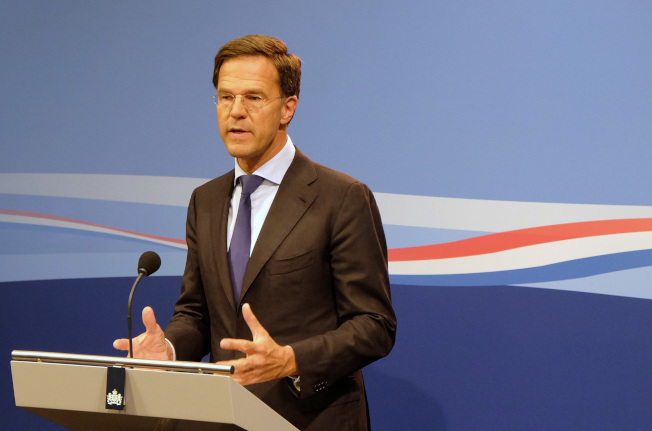 荷蘭總理呂特親手清理自己打翻的咖啡,獲網友稱讚。(美聯社)