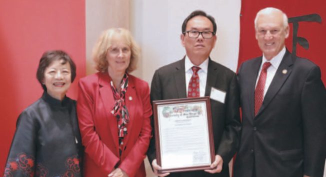 聖地牙哥縣政委員會聯名表彰華人僑領余建強(右二),由羅伯茨(右一)代表頒狀,肯定余氏家族的貢獻。(余建強提供)