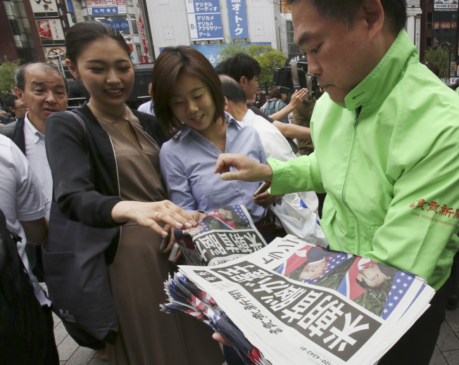 川普在新加坡會見金正恩,牽動人心。日本媒體「讀賣新聞」12日在街上發售川金會的號外,路人爭相購閱。(美聯社)