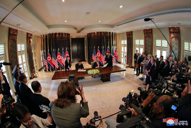 在國際媒體見證下,川普總統與北韓領導人金正恩,12日在新加坡簽署共同聲明。(美聯社)