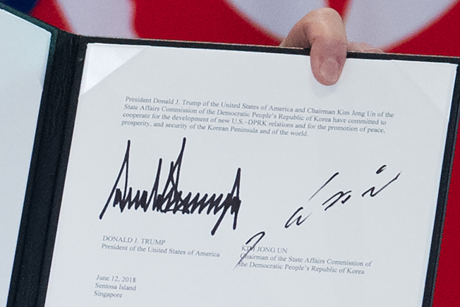 川普總統展示他與金正恩12日在新加坡簽署聯合聲明上的兩人簽名。(Getty Images)