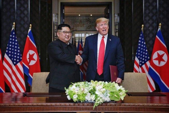 美国总统川普(右)12日与北韩领袖金正恩(左)在新加坡举行历史性峰会,两人共同在媒体面前签署文件后握手致意。新加坡通讯及新闻部提供