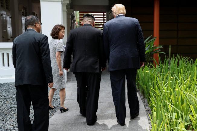 川普總統與北韓金正恩12日兩人同行交談,參加工作午餐。左為隨行翻譯。(路透)