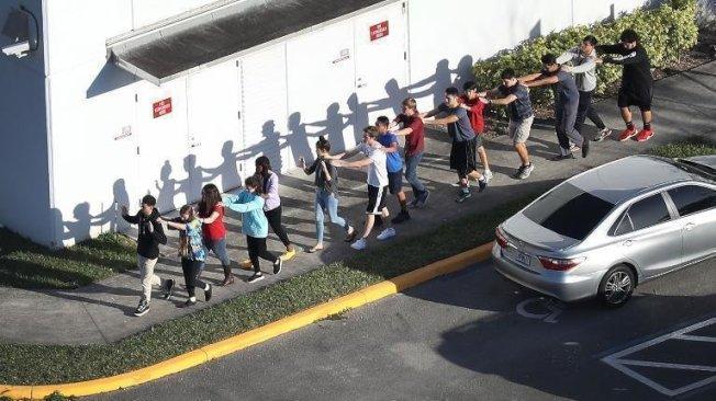 佛州道格拉斯高中發生槍案後,警察組織學生們有序撤離,場面震撼。(教育記者協會提供)