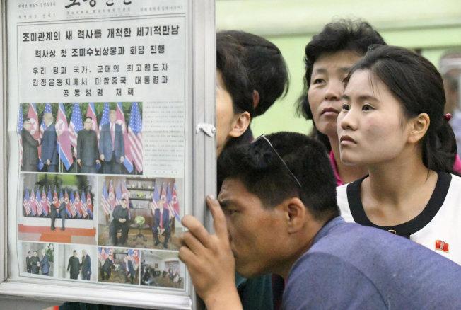 北韓民眾在平壤的地鐵站公告牌爭睹川金會的報導。(路透)