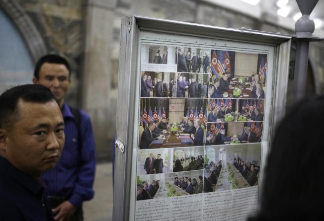 北韓民眾在平壤的地鐵站公告牌爭睹川金會的報導。(美聯社)