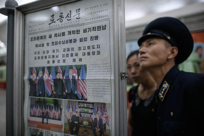 一名北韓地鐵列車長在平壤的復興地鐵站仔細閱讀張貼的川金會新聞。北韓官方報紙在頭版刊登多張北韓領袖金正恩與美國總統川普歷史性峰會的照片。(Getty Images)