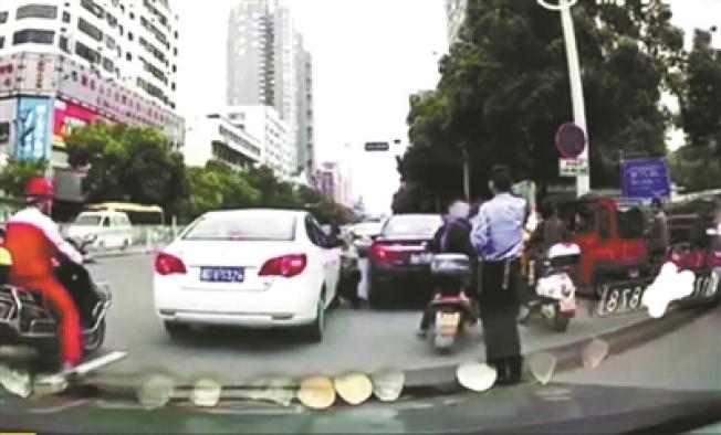 身著警服的男子突然倒在一輛白色轎車的右前部。(視頻截圖)