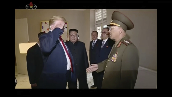 川普總統(左)在新加坡會見北韓代表團時,北韓人民武力省部長努光鐵(右)舉手向川普行軍禮;努光鐵伸手時,川普也向努光鐵回禮,然後兩人握手。(美聯社)