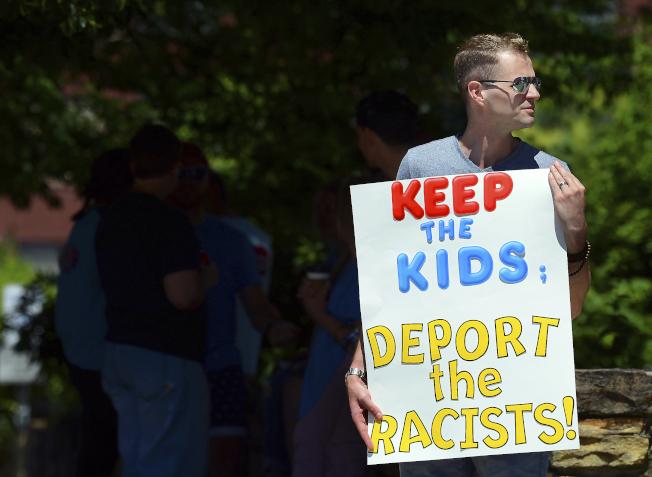 賓州維權人士舉起標語牌,要求「遣返種族主義者,讓孩子留下」。(美聯社)