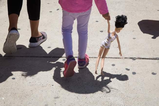 大批婦女小孩的無證移民,17日自德州McAllen市的移民局拘留中心釋放後,在附近的天主教收容中心,等候安頓。一位小女孩跟著母親拖著玩具走,前途未卜。(Getty Images)