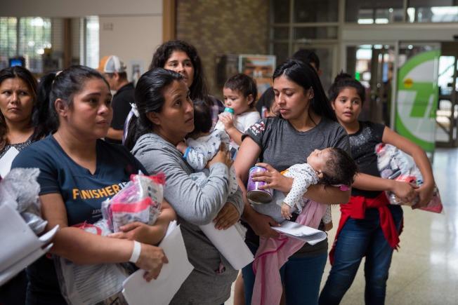大批婦女小孩的無證移民,17日自德州McAllen市的移民局拘留中心釋放後,在附近的天主教收容中心,等候安頓。(Getty Images)