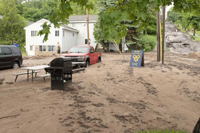 連續兩天的豪雨在中西部的北方地區造成洪水氾濫,道路被沖垮,商店受損,還在多處形成數十個深水鴻溝,至少一人被淹死。圖為密西根州霍頓鎮一處道路被泥沙覆蓋。(美聯社)
