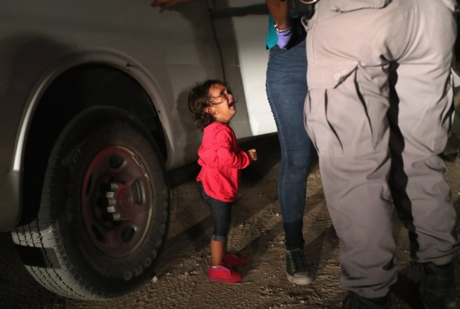 這張由曾獲普立茲新聞攝影獎記者約翰摩爾所拍的兩歲宏都拉斯小女娃的照片,成為這次拆散偷渡客家庭風波的象徵性標誌。這位女娃的母親被移民局探員帶走,留下她不知所措,駭然大哭。(Getty Images)