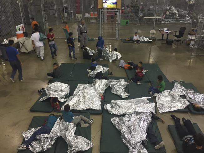 非法入境的中南美偷渡客被關押在德州移民執法單位臨時安排的拘留中心,睡在當局提供的保暖床單上。(Getty Images)