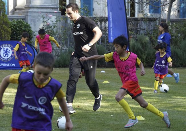 英格蘭退役足球員蘭帕德(Frank Lampard,中)去年在英國駐東京大使館教青少年踢球。(美聯社)