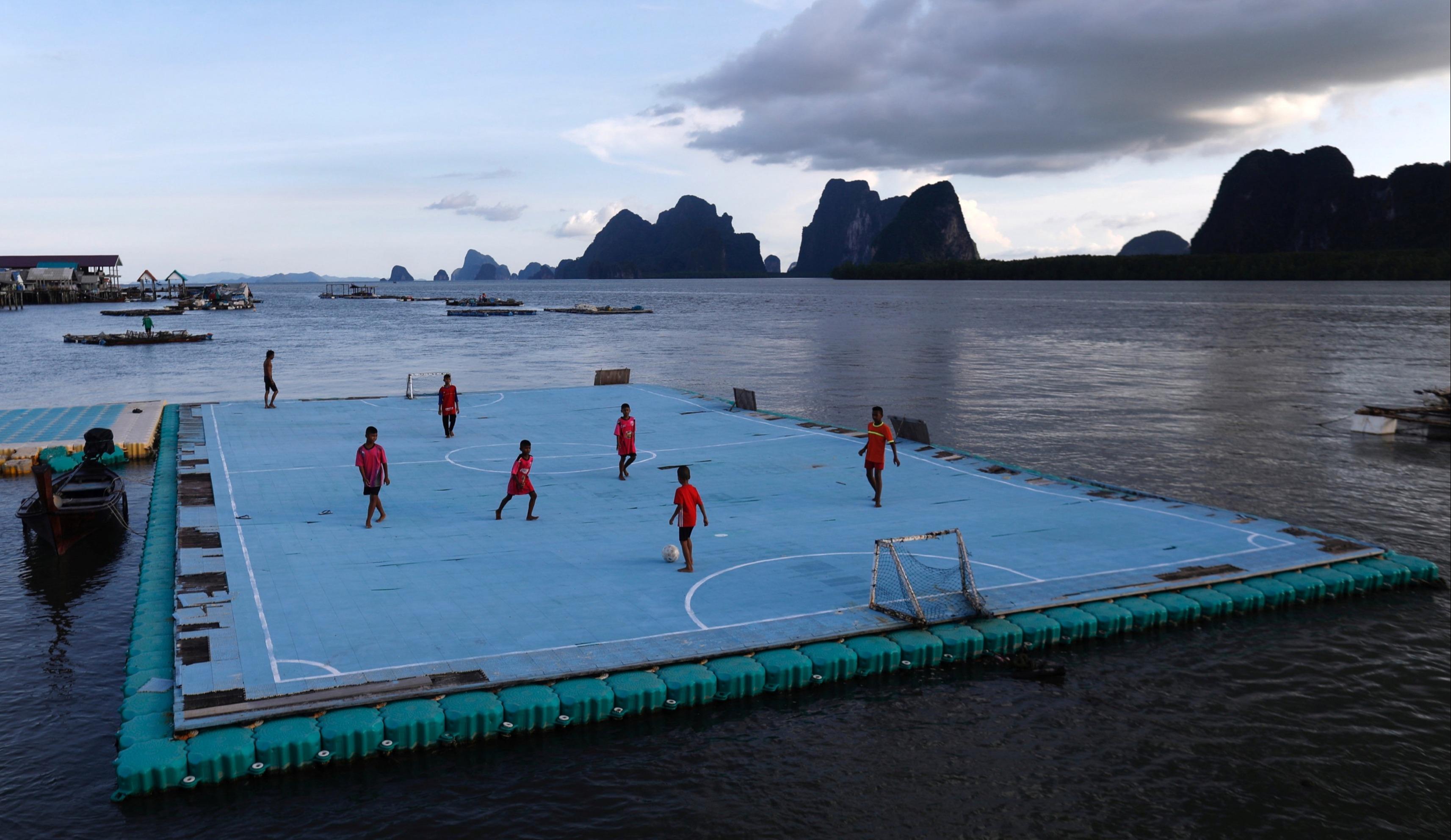 一群青少年在泰國攀牙府的漂浮球場上踢球。(路透)