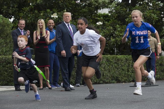 白宮5月30日舉行運動健身日活動,職員小孩在白宮園區賽跑。川普總統(中)、第一千金伊凡卡(後排左二)等人在後方拍手,替參賽者加油。(歐新社)