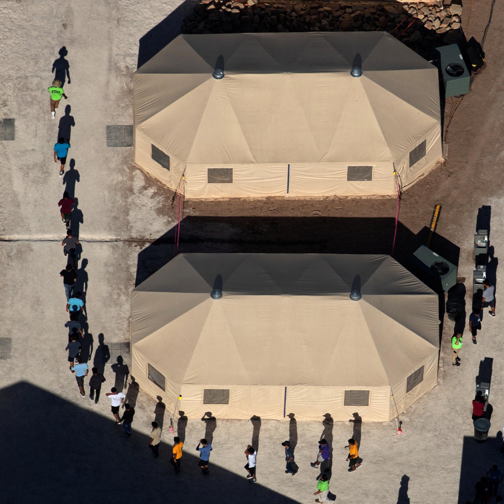 德州托提洛收容的兒童在帳篷外排成一列。(路透)