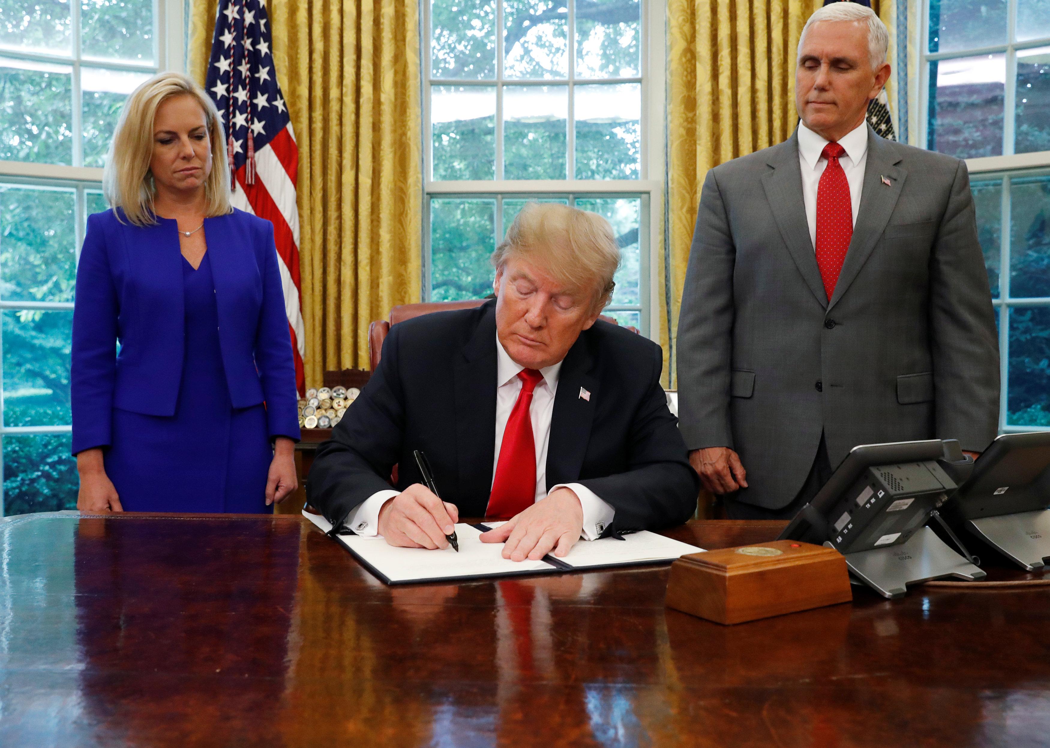 川普總統政策轉彎,在白宮簽署行政令,改變移民家庭處理原則。右立者為副總統潘斯,左立者為國土安全部長尼爾森。(路透)