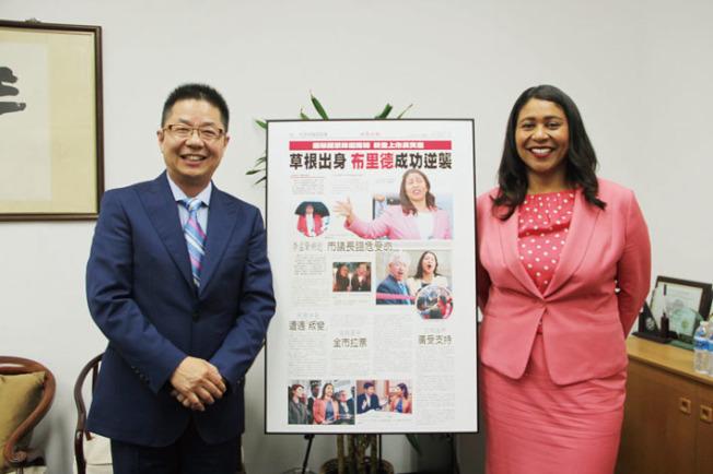 社長駱焜祺(左)致贈本報刊出的布里德「勝選之路」專題報導紀念版,恭喜她當選。(記者李晗/攝影)