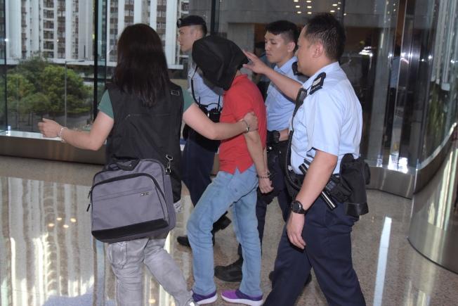 香港太古城鰂魚涌公園26日發生一起驚人槍擊案,被捕女子(紅衣)由警方帶走。(中通社)