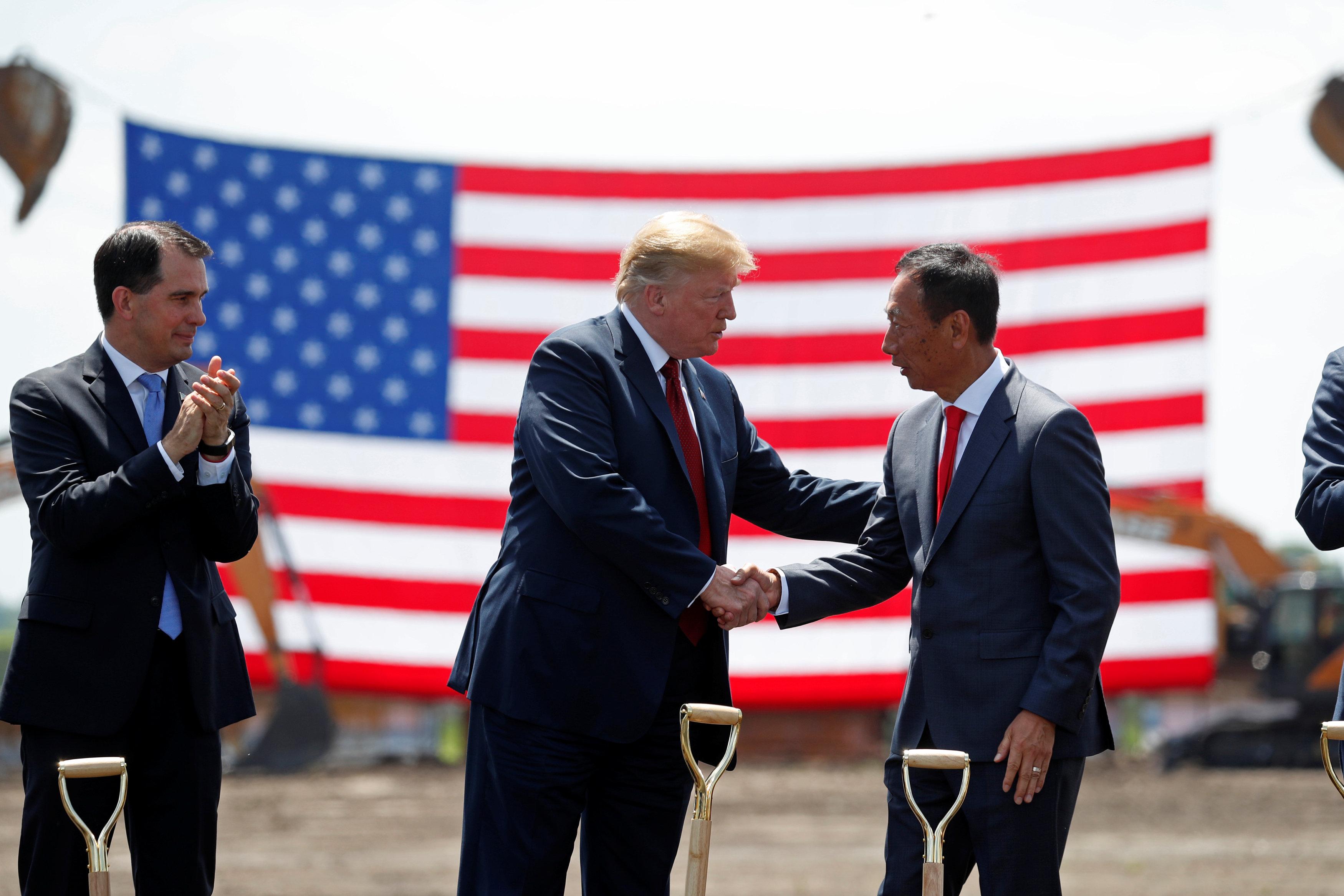 川普總統(中)飛往威斯康辛州,為富士康美國園區動土,並與鴻海董事長郭台銘握手,左為威州州長沃克。(路透)