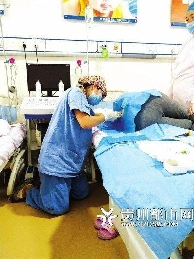 一名懷孕的麻醉科女醫師大腹便便,跪在地上給孕婦施打無痛分娩針。取自貴州都市報