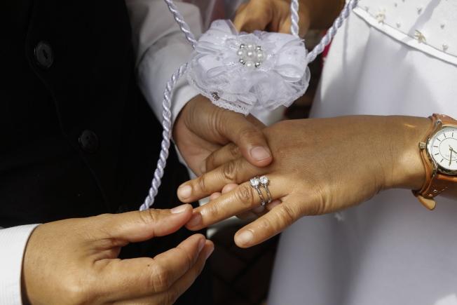 夫妻戴上戒指,情定終生。(歐新社示意圖)