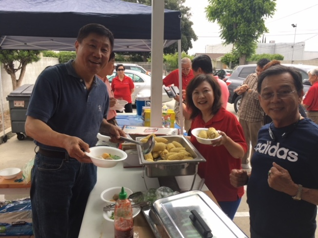 邱啟宜(左)和林鳳英夫婦為比賽選手和工作人員準備食品,忙的不亦樂乎。(記者楊青/攝影)
