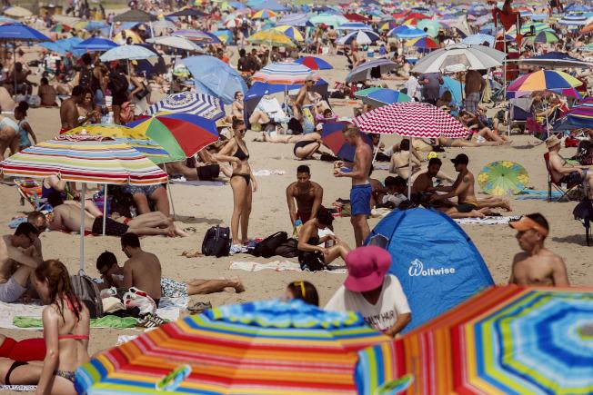 全美多地氣溫在1日破百,紐約市皇后區濱大西洋的洛克威爾海灘1日擠滿消暑人潮。(美聯社)