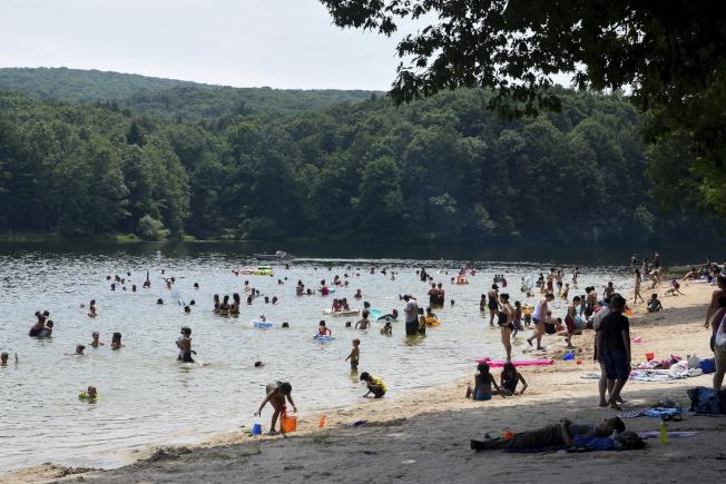民眾1日在賓州一處湖邊戲水解暑。(美聯社)