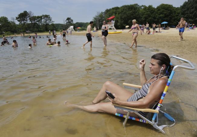 新州居民坐在水中納涼。(美聯社)