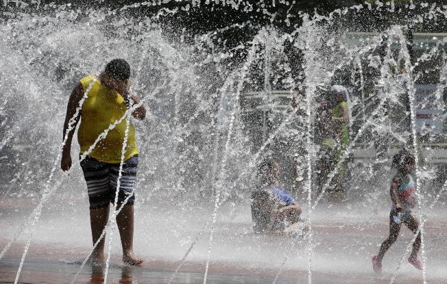 最近幾天使全國廣大地區揮汗如雨的熱浪愈演愈烈,一直到本周末,中部和東部地區將陷入危險的創紀錄高溫。圖為波士頓的居民在噴泉的水柱中降溫。(美聯社)