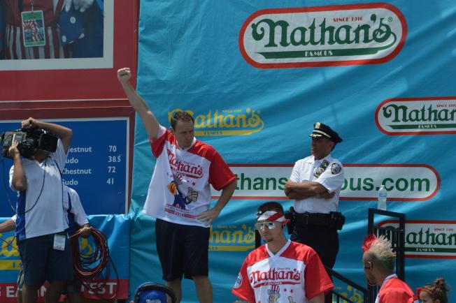 切斯納(舉手者)第11次奪得「Nathans國際吃熱狗大賽」男子組冠軍。(記者牟蘭/攝影)