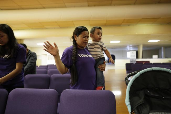 丈夫面臨遣返的一名婦女,抱著兒子在俄亥俄州一所教會禱告。(美聯社)