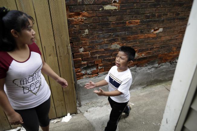 圖為肯塔基州一名無證客的兒子沒看到爸爸哭起來,媽媽趕忙安慰他。(美聯社)
