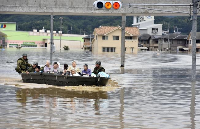 救難人員使用救生艇協助倉敷市的年長居民從災區脫困。(美聯社)