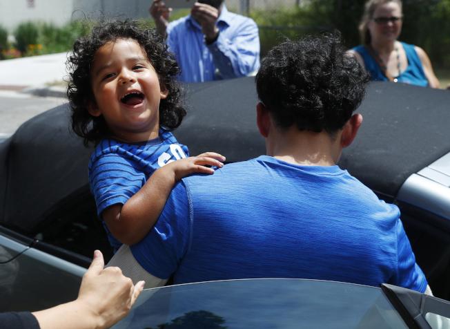 來自宏都拉斯的馬西亞10日在密西根州的大湍市和兒子團聚後,抱著孩子登車離去。(美聯社)