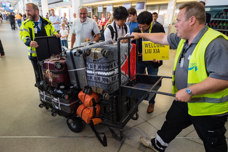 機場工作人員把劉霞的行李送出機場。(路透)